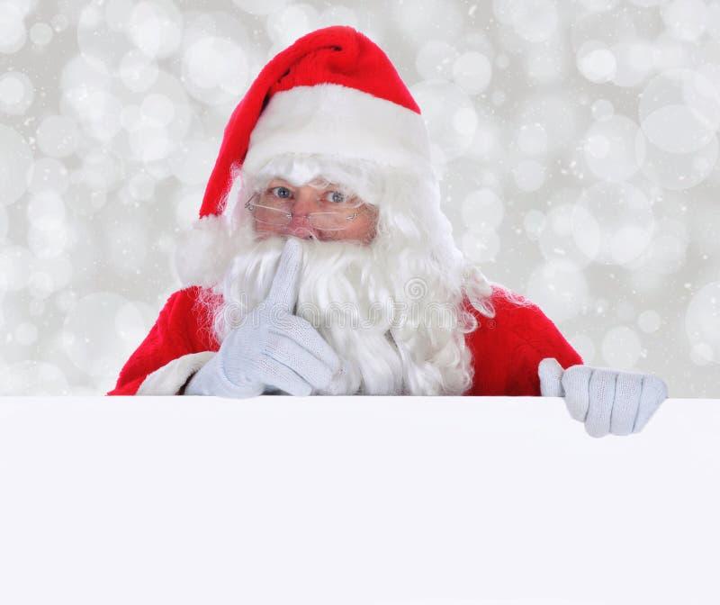 Santa Claus med ett tomt tecken som gör Shh gest fotografering för bildbyråer
