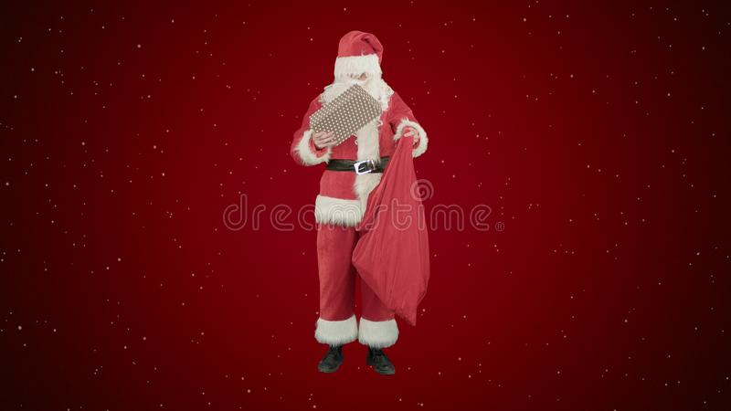 Santa Claus med hans säck av massor av gåvor på röd bakgrund med snö arkivfoton