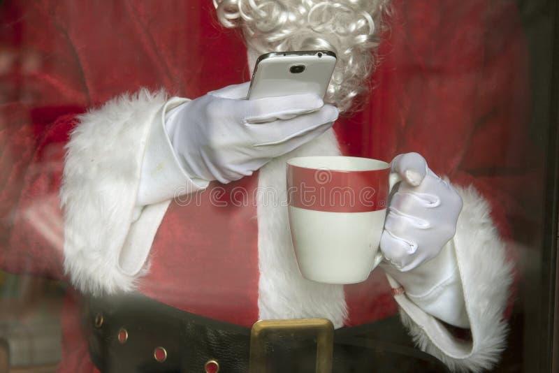 Santa Claus med smartphonen royaltyfria bilder