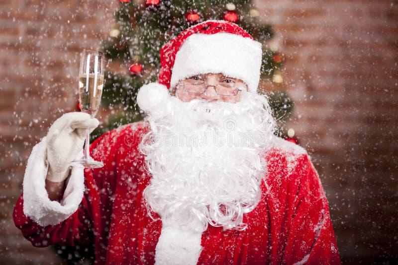 Santa Claus met een glas mousserende wijnchampagne stock foto's