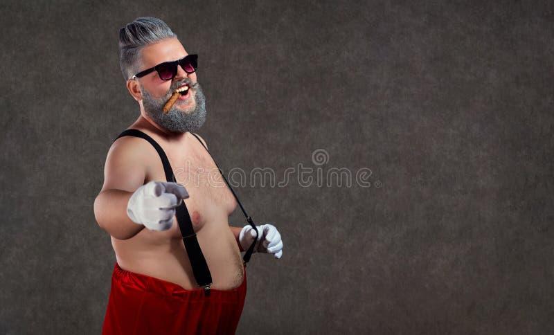 Santa Claus met een naakte buiksigaar in zijn tanden tegen stock fotografie