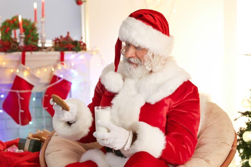 Santa Claus met koekje en glas melk in ruimte voor Kerstmis wordt verfraaid die royalty-vrije stock afbeeldingen
