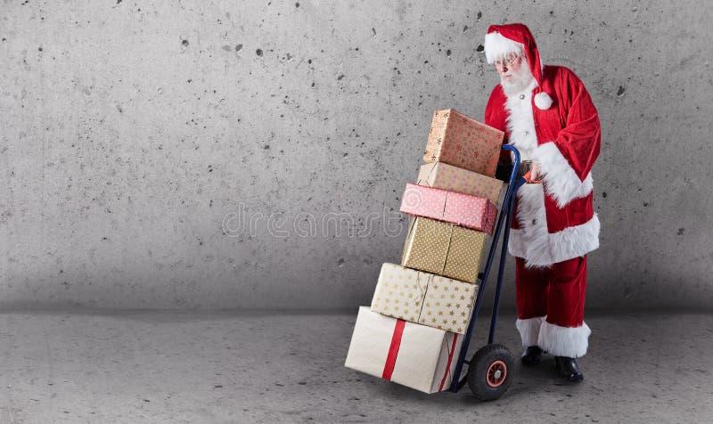 Santa Claus met stelt gestapeld op een leveringskarretje met een duidelijke ruimte als achtergrond en exemplaar voor royalty-vrije stock foto