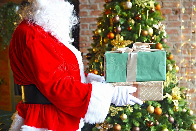 Santa Claus mettant secrètement des boîte-cadeau par l'arbre de Noël photographie stock