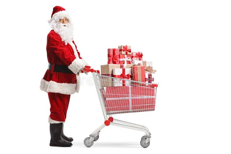 Santa Claus mit einem Einkaufswagen mit Geschenken stockfoto