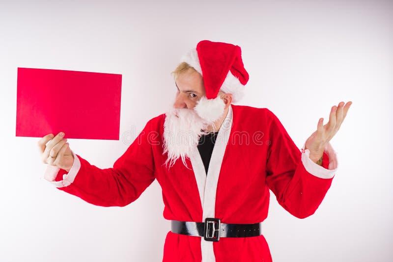 Santa Claus mit einem Zeichen auf einem weißen Hintergrund Das Konzept von Rabatten und von Verkäufen für Weihnachten Leerer Plat stockfotografie