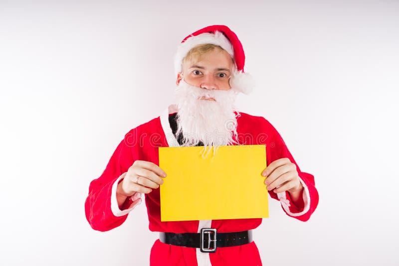Santa Claus mit einem Zeichen auf einem weißen Hintergrund Das Konzept von Rabatten und von Verkäufen für Weihnachten Leerer Plat lizenzfreie stockbilder