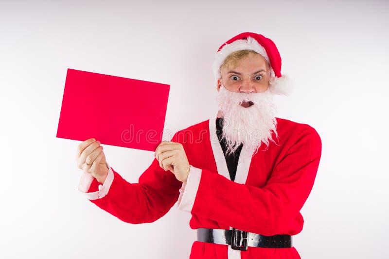 Santa Claus mit einem Zeichen auf einem weißen Hintergrund Das Konzept von Rabatten und von Verkäufen für Weihnachten Leerer Plat lizenzfreie stockfotos