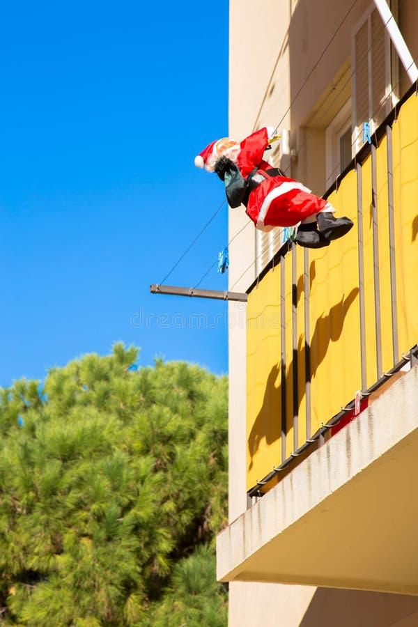 Santa Claus mit Geschenktasche klettert die Wand des Hauses lizenzfreie stockfotos