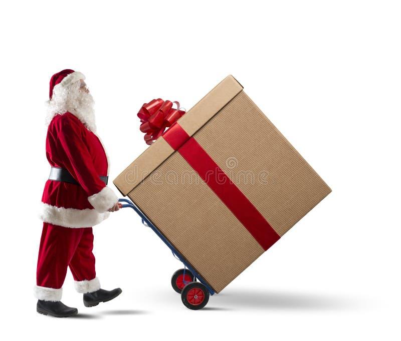 Santa Claus mit großem Weihnachtsgeschenk stockbilder