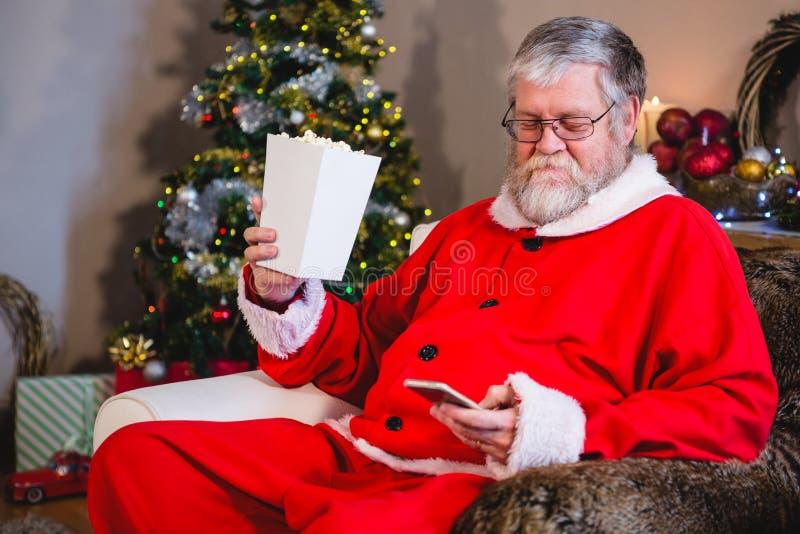 Santa Claus-mobiel gebruiken terwijl het hebben van popcorn stock fotografie