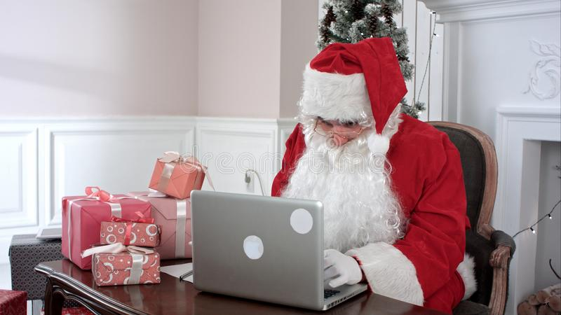 Santa Claus moderna que trabaja en su ordenador portátil y que prepara presentes foto de archivo