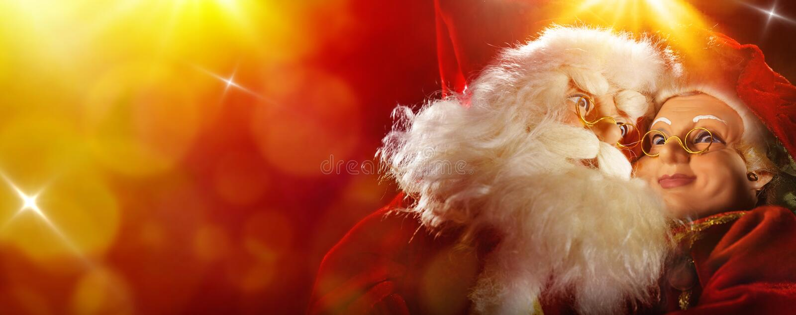 Santa Claus and Mrs Claus on red and yellow background. Santa Claus and Mrs. Claus clinging on red and yellow background with lights and shines royalty free stock images