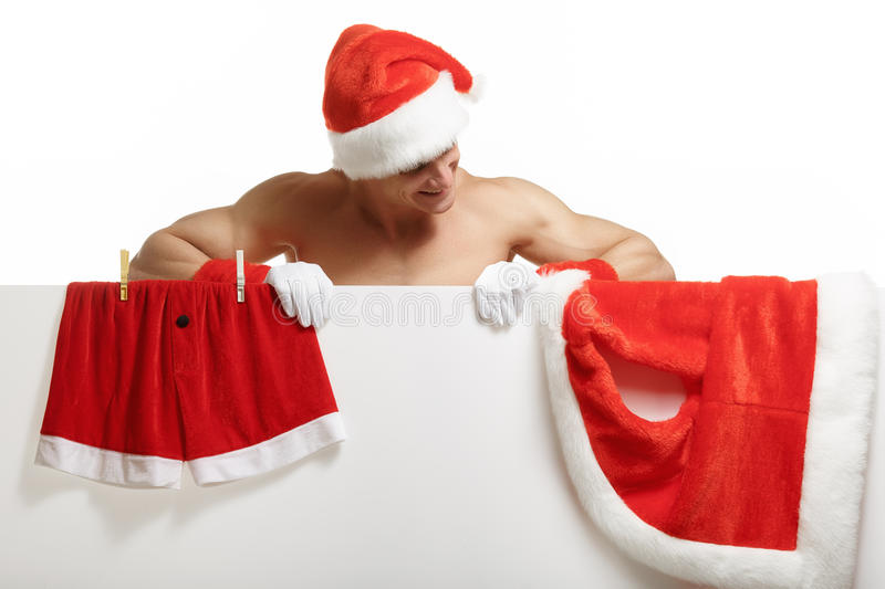 Santa Claus muscular hung his clothes on a banner sales royalty free stock images