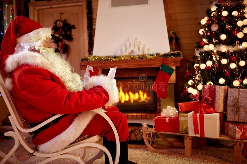 Santa Claus na sala perto da chaminé leu a lista desejoso para Cristo foto de stock royalty free