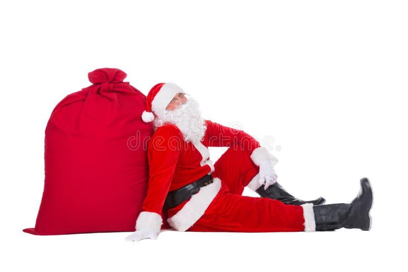 Santa Claus nahe großem rotem Weihnachtssack voll Geschenken und Geschenken am neuen Jahr lokalisiert auf weißem Hintergrund lizenzfreies stockbild