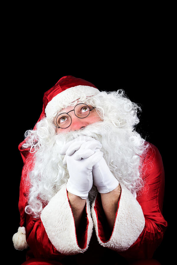 Santa Claus nella notte di Natale che prega sul BAC nero fotografie stock