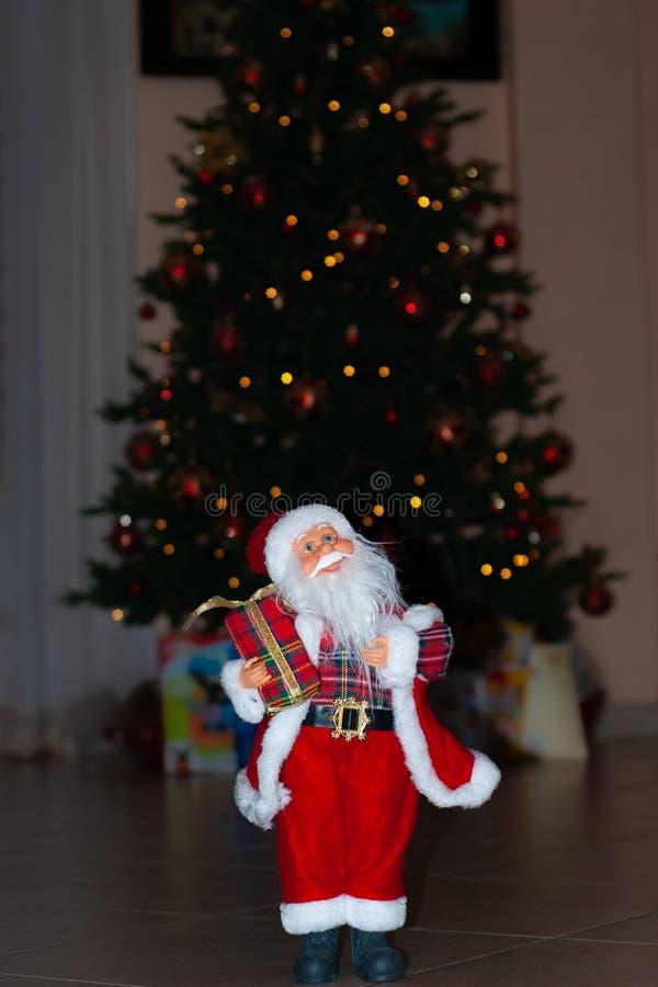 Santa Claus no tempo do Natal com árvore, presentes e bokeh imagem de stock