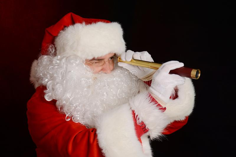 Santa Claus no terno tradicional que guarda o telescópio pequeno fotografia de stock royalty free