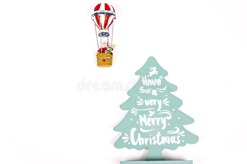 Santa Claus no voo do balão de ar quente até uma árvore verde de madeira com o Feliz Natal escrito sobre fotografia de stock