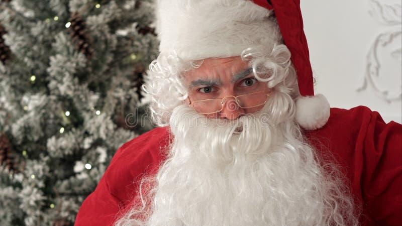 Santa Claus nos monóculos que puxam as caras engraçadas e o riso imagens de stock royalty free