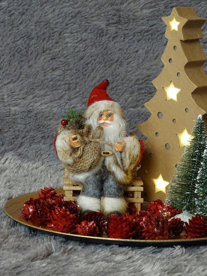 Santa Claus obsiadanie na banku otaczającym drzewami i pineappels obraz stock