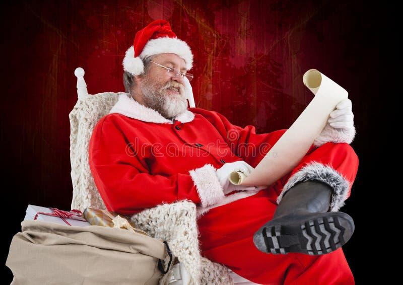Santa Claus obsiadanie na czytelniczej liście życzeń i krześle obrazy royalty free
