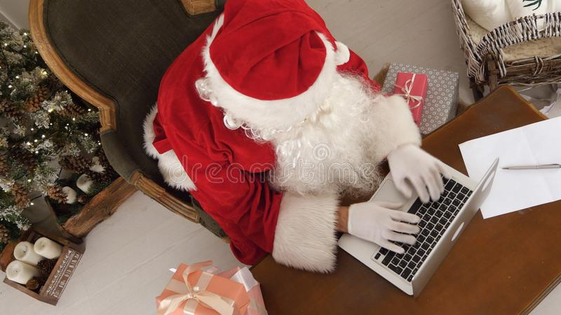 Santa Claus occupée faisant une liste des présents sur son ordinateur portable photo libre de droits