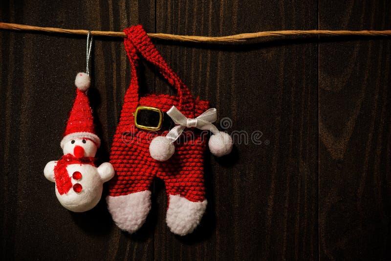Santa Claus och snögubbe som haning på den mörka wood väggen royaltyfria foton