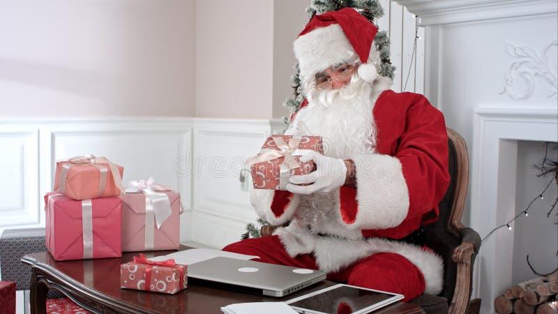 Santa Claus ocupada que prepara presentes usando o portátil e a tabuleta digital, classificando suas letras e recebendo um presen fotografia de stock royalty free