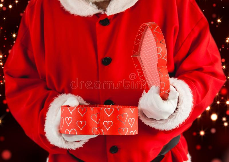 Santa claus opening a gift box. Mid section of santa claus opening a heart shaped gift box stock images