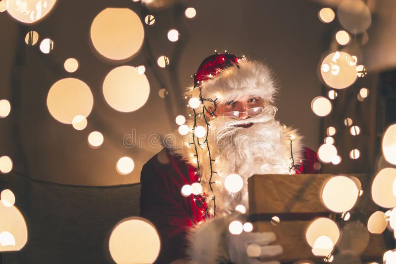 Santa Claus opening glowing gift box. Santa Claus sitting on the couch in warm holiday home atmosphere, opening magic glowing gift box with Christmas lights and stock image