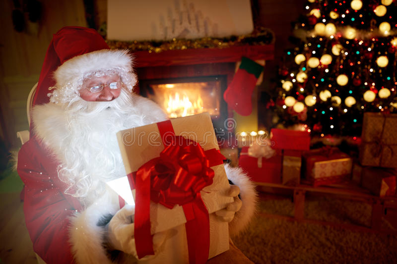 Santa Claus opening a magic gift box. And let out atmosphere of a Christmas royalty free stock images