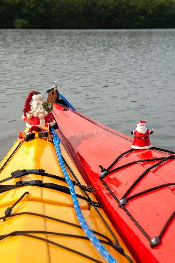 Santa Claus ornaments decorate holiday kayaks. Santa Claus ornaments decorate kayaks in the water at Christmas on Sanibel Island, Florida stock images