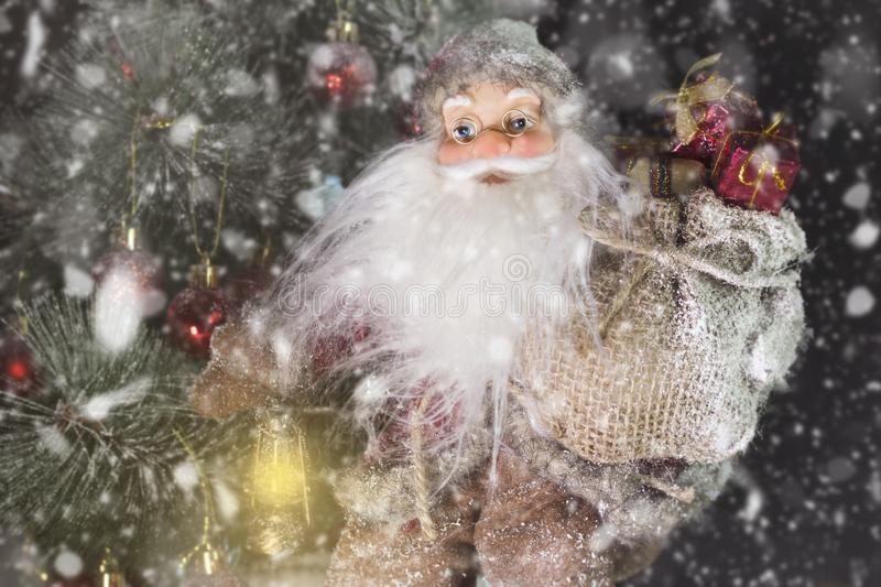 Santa Claus Outdoors Beside Christmas Tree em levar da queda de neve fotografia de stock royalty free