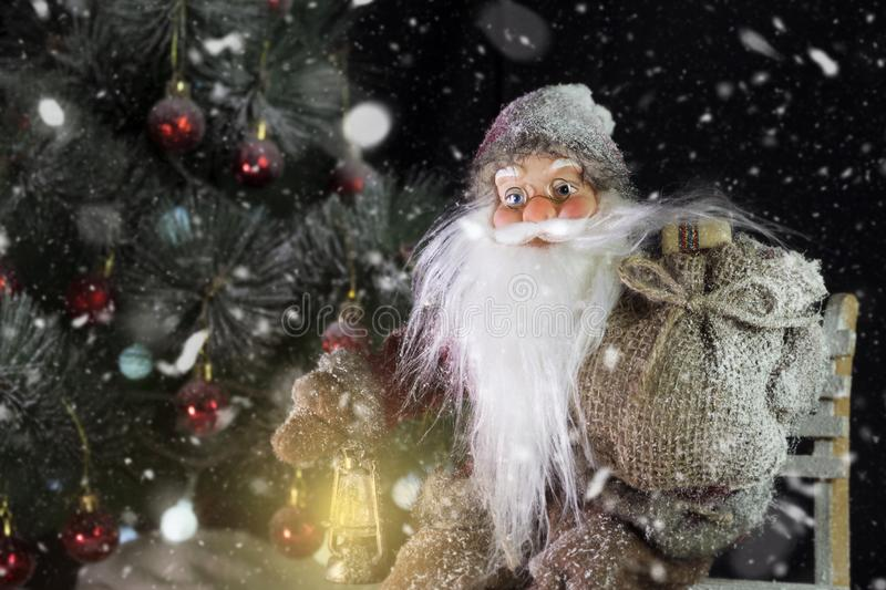 Santa Claus Outdoors Beside Christmas Tree em levar da queda de neve fotos de stock royalty free