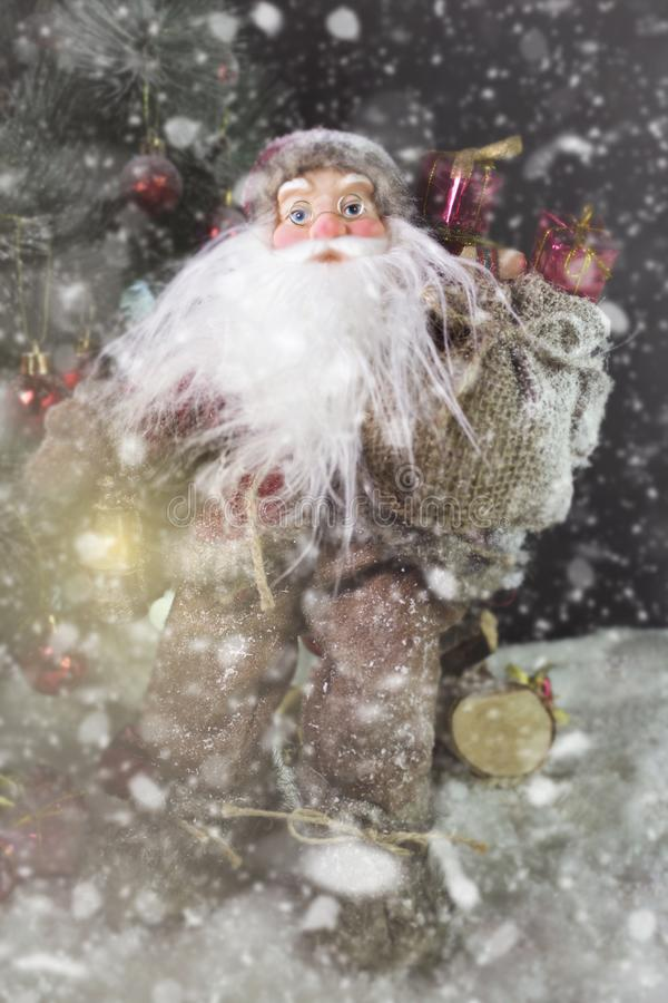 Santa Claus Outdoors Beside Christmas Tree em levar da queda de neve fotografia de stock