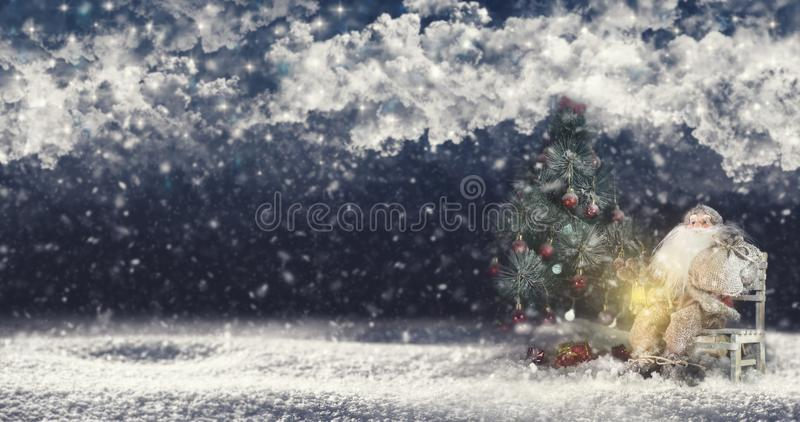 Santa Claus Outdoors Beside Christmas Tree em levar da queda de neve imagem de stock royalty free