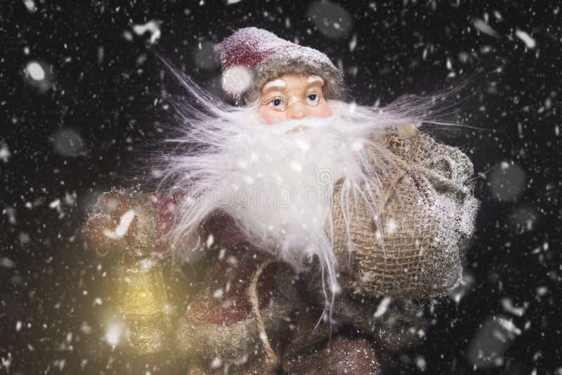 Santa Claus Outdoors Beside Christmas Tree nel trasporto delle precipitazioni nevose immagine stock