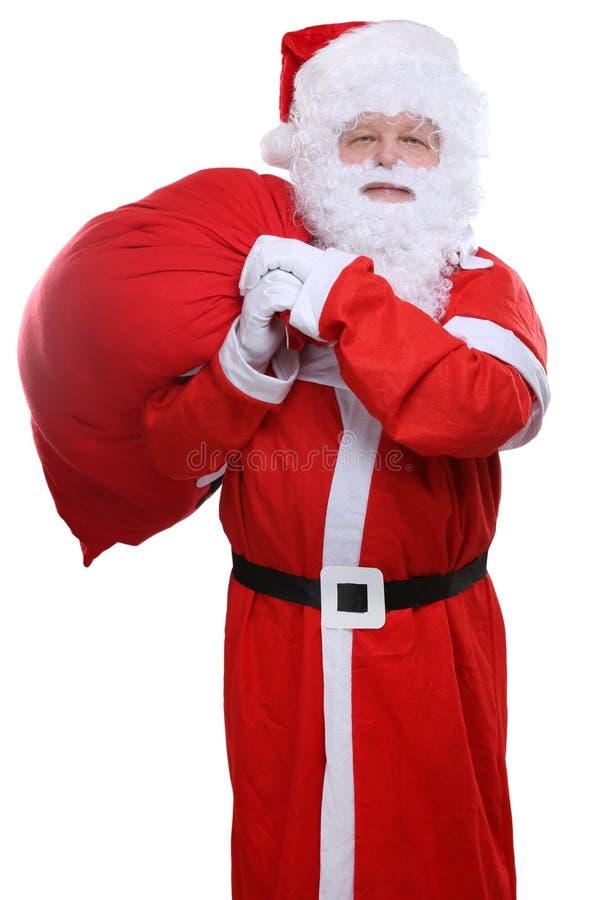 Santa Claus påse på tillbaka julgåvor som isoleras på vit arkivbild