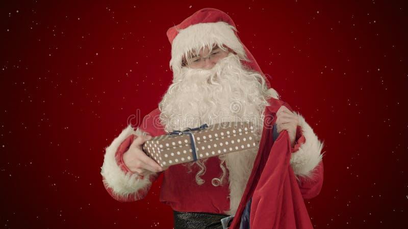 Santa Claus Packaging Gifts en fondo rojo con nieve imagen de archivo