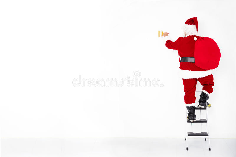 Santa claus painting on blank wall royalty free stock image