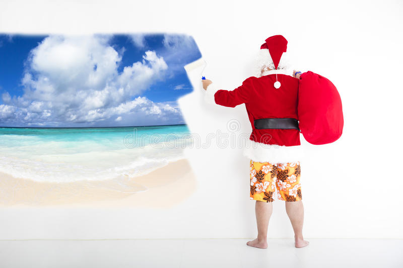 Santa claus painting vacation concept on wall. Santa claus with beachwear and painting vacation concept on the wall royalty free stock photography