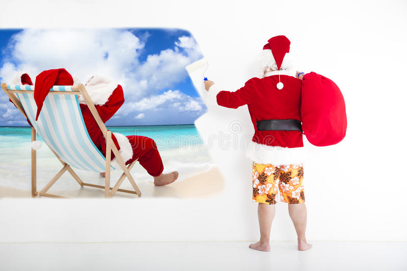 Santa claus painting vacation concept on wall. Santa claus with beachwear and painting vacation concept on wall stock photo