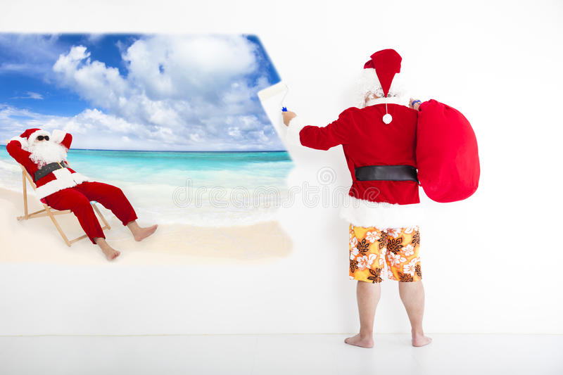 Santa claus painting vacation concept on wall. Santa claus with beachwear and painting vacation concept on wall stock photography