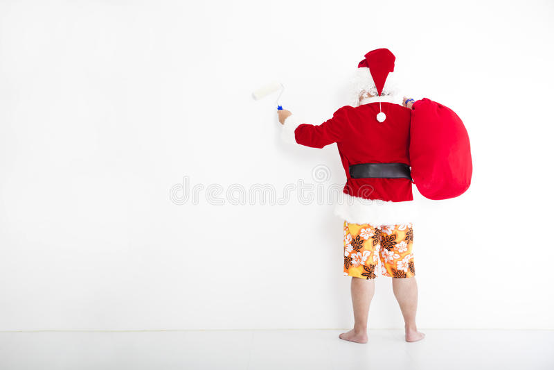 Santa claus painting on the white wall. Santa claus with beachwear and painting on the white wall royalty free stock photography