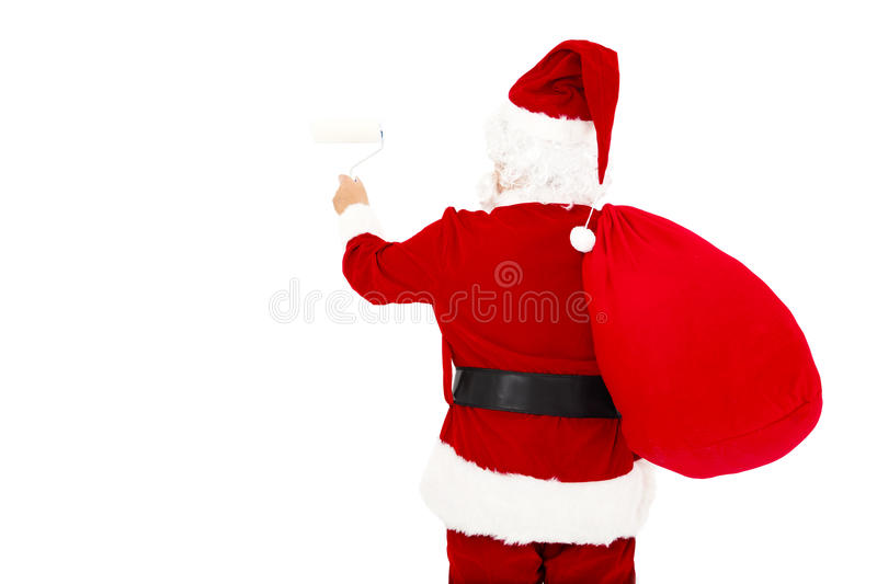 Santa claus painting on white wall. Rear view of santa claus painting on white wall royalty free stock photography