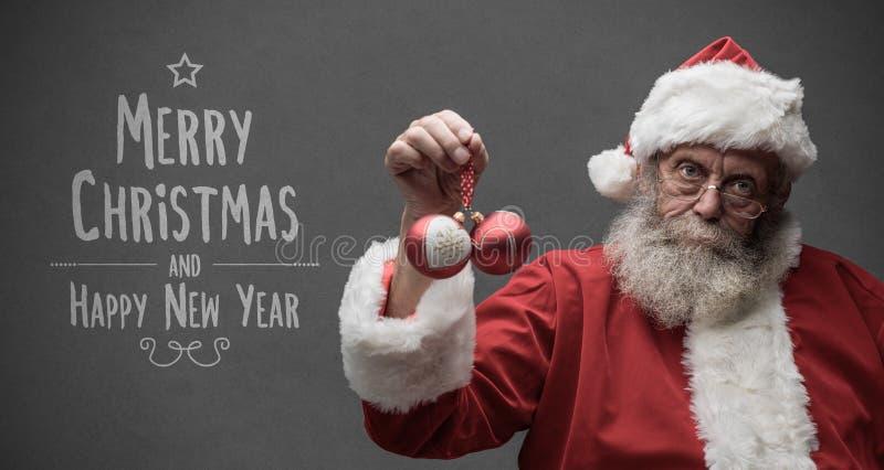 Santa Claus paresseuse tenant des boules de Noël photographie stock