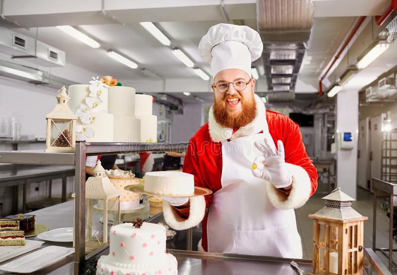 Santa Claus a pastry cooks a cake in the kitchen on Christmas Da royalty free stock photo