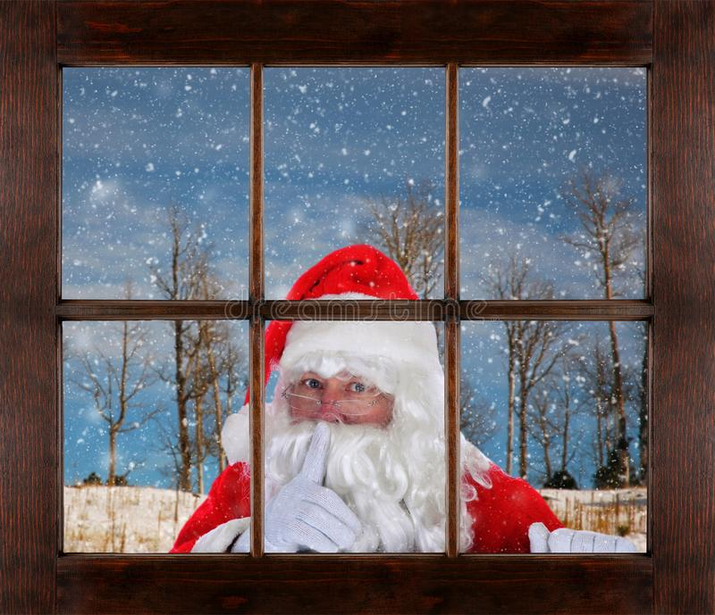 Santa Claus peeking in window making Shh sign, finger to mouth, with snowy winter scene in the background.  royalty free stock images
